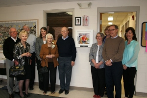 Jean Ross, her family, and members of Marion School District staff posing with their new AED