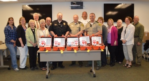 The Veterans Memorial Health Care Foundation gifted defibrillators to many local law enforcement officials last week following the successful community direct mail fund drive held last fall.  Each Allamakee County deputy as well as the Monona Police Department received a defibrillator for their vehicle to ensure CPR and defibrillation is quickly accessible in all sections of the Veterans Memorial Hospital service area.  Pictured, in front middle receiving the defibrillators are Brian Berger of the Monona Police Department; Clark Mellick, Allamakee County Sheriff, and Barry Olson, Allamakee County Deputy.  Also pictured, left to right are Veterans Memorial Health Care Foundation members Amy Cote'-Hill, Lori Bahr-Stevenson, Nona Sawyer, Craig Lensing, Gloria Krambeer, Wayne Burke, Jeff Mitchell, EMT-P, EMS Supervisor, Veterans Memorial Hospital, Jackie Halverson, Nancy Schoh, Jane Dietrich, Paula Kerndt Wickham, President of First Voice who supplied the defibrillators, and Dennis Lyons also of the Foundation.